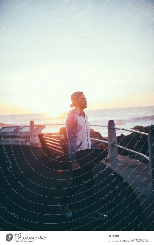 Männlicher Hippie-Erwachsener, der in Sonnenuntergang mit longboard auf Promenade geht Lifestyle Stil Freude Freizeit & Hobby Abenteuer Freiheit Kreuzfahrt Meer