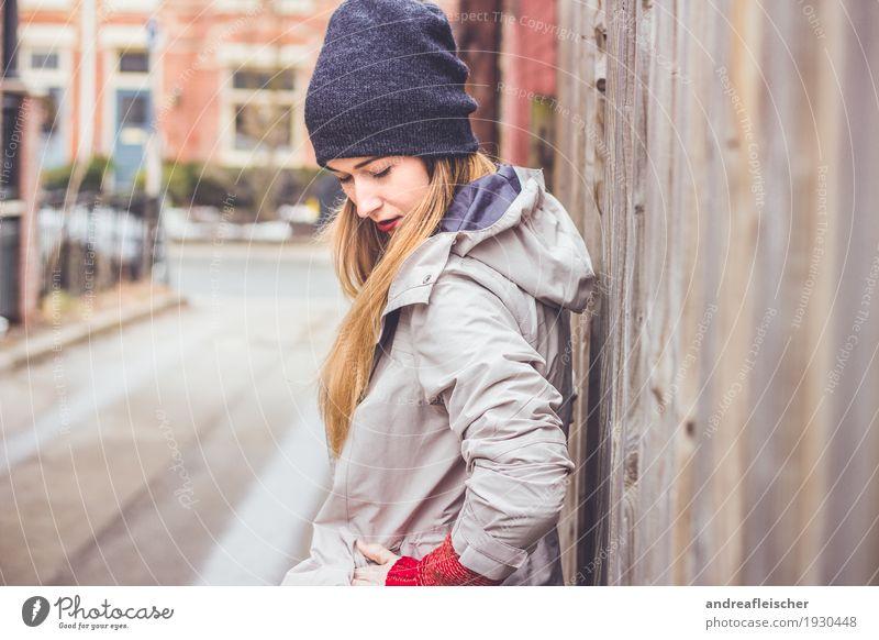 Junge Frau wartet am Holzzaun auf ihren Freund Lifestyle Ausflug Städtereise feminin Jugendliche 1 Mensch 18-30 Jahre Erwachsene Pullover Jacke Mütze blond