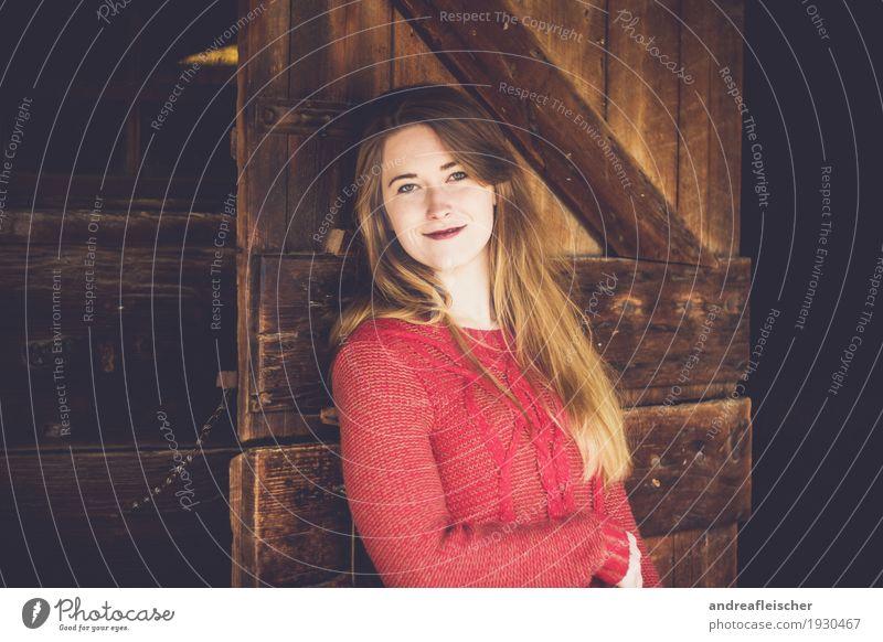 Junge Frau lehnt an Holztür und ist glücklich feminin Jugendliche Leben 1 Mensch 18-30 Jahre Erwachsene Pullover brünett blond langhaarig Scheitel Pony