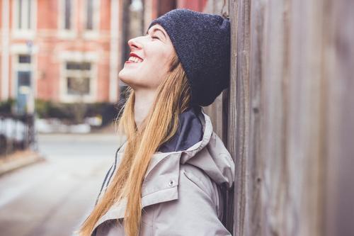 Junge Frau lehnt an Holzaun und ist glücklich feminin Leben 1 Mensch 18-30 Jahre Jugendliche Erwachsene Kleinstadt Stadtrand Jacke Mütze blond langhaarig lachen