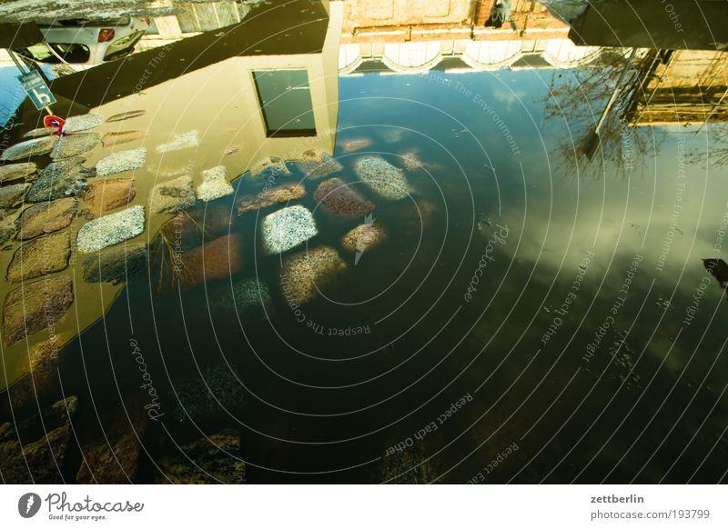 Füddse Pfütze Wasser Wasseroberfläche Reflexion & Spiegelung Pflastersteine Kopfsteinpflaster Haus Gebäude