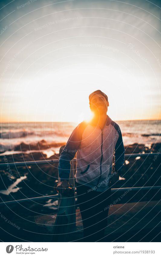 Junger Hippie-Erwachsener mit longboard im Sonnenuntergang auf Promenade Lifestyle Stil Freude Freizeit & Hobby Meer Wellen Sport Mensch maskulin Junger Mann