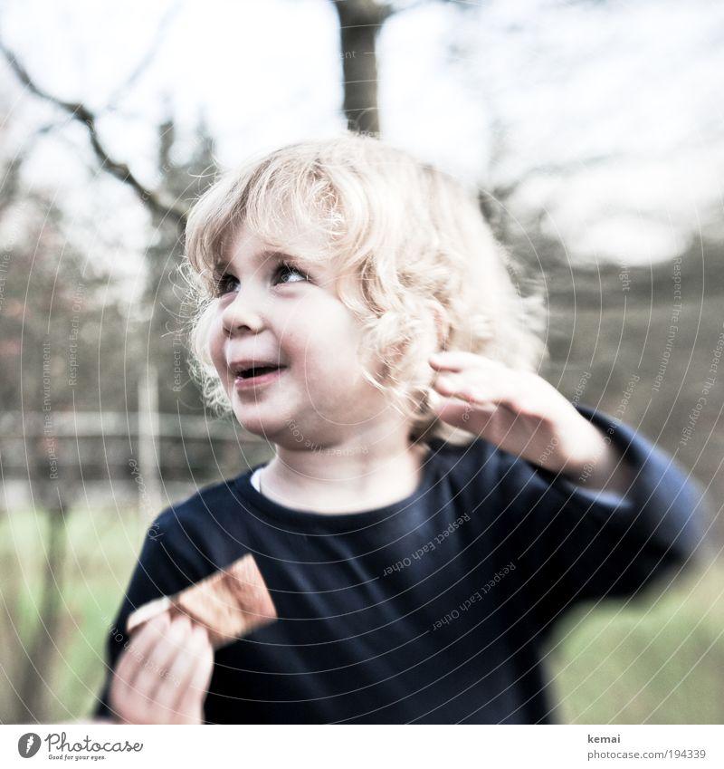 Der Schokoriegel Mensch Kind Kleinkind Mädchen Kindheit Kopf Haare & Frisuren Gesicht Hand 1 1-3 Jahre blond langhaarig Locken Essen genießen Lächeln lachen
