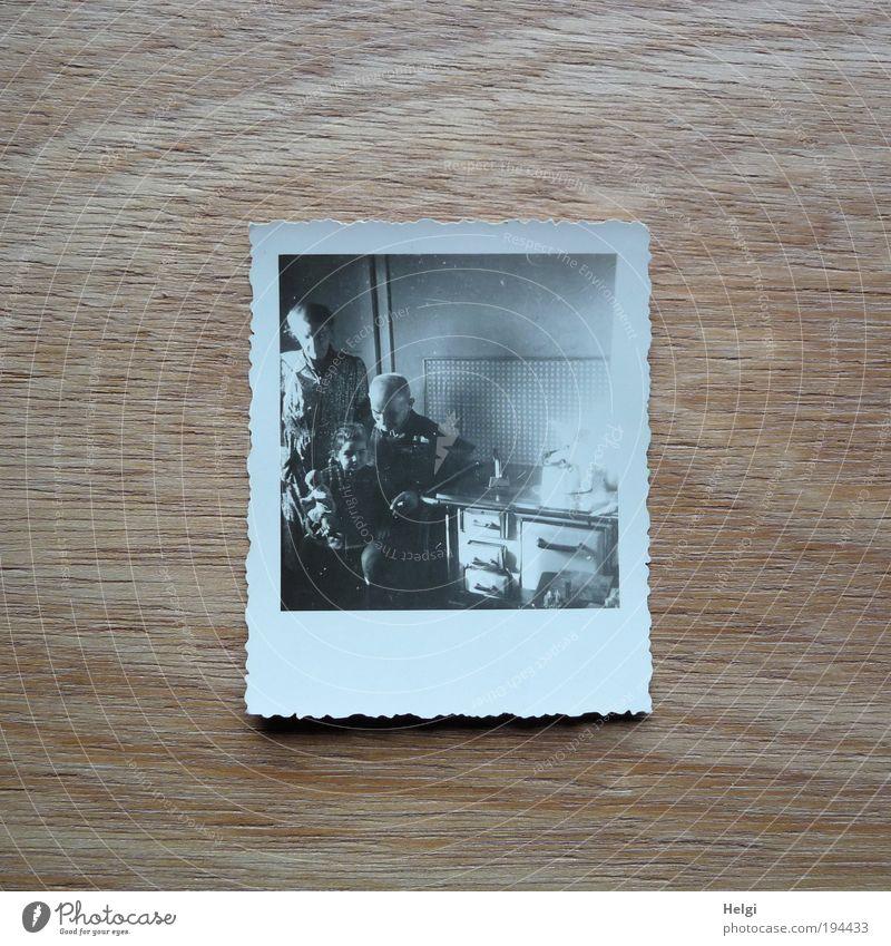 Foto eines Fotos in einer historischen Küche  mit Opa, Mutter, Kind und Puppe Mensch maskulin Frau Erwachsene Mann Weiblicher Senior Männlicher Senior Kindheit