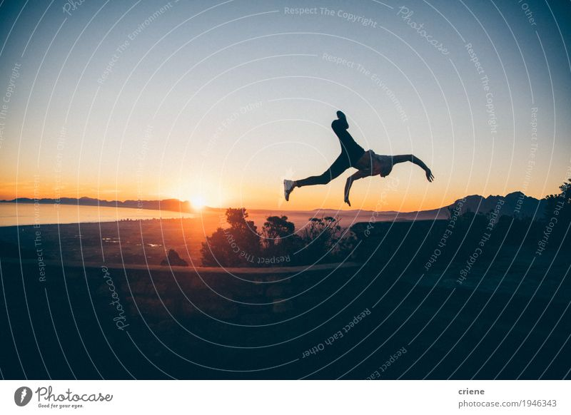 Schattenbild des jungen erwachsenen Mannes, der hoch in Sonnenuntergang springt Lifestyle Freude Ferien & Urlaub & Reisen Abenteuer Freiheit Sommer