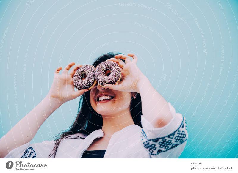 Kaukasische Frauen, die lustiges Gesicht mit Schokoladenschaumgummiringen machen Lebensmittel Kuchen Dessert Süßwaren Essen Lifestyle Freude Mensch feminin