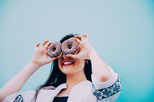 Kaukasische Frauen, die lustiges Gesicht mit Schokoladenschaumgummiringen machen Mensch Jugendliche blau Junge Frau Freude Erwachsene Essen Lifestyle feminin