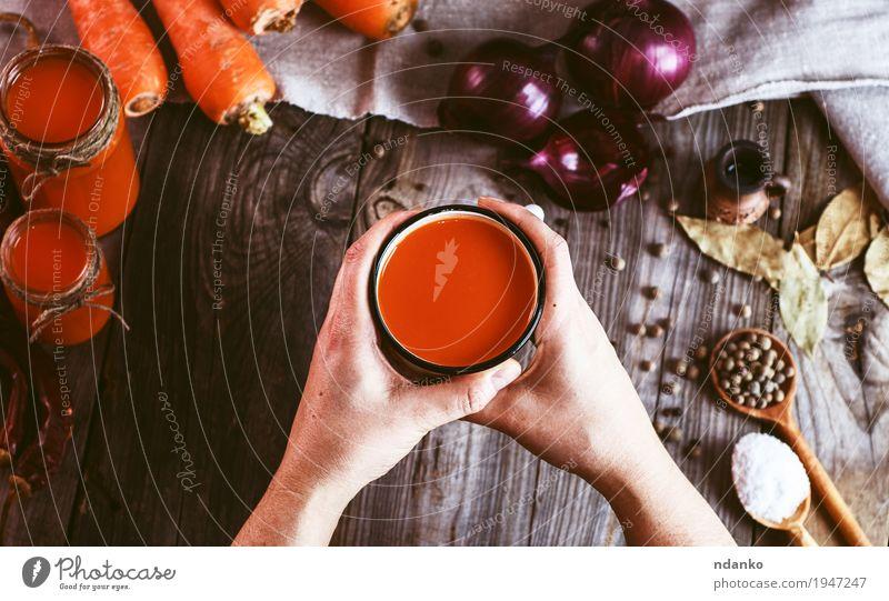 weibliche Hände, die einen Eisenbecher mit Karottensaft halten Mensch Frau Jugendliche Hand Blatt 18-30 Jahre Erwachsene Essen Holz Lebensmittel