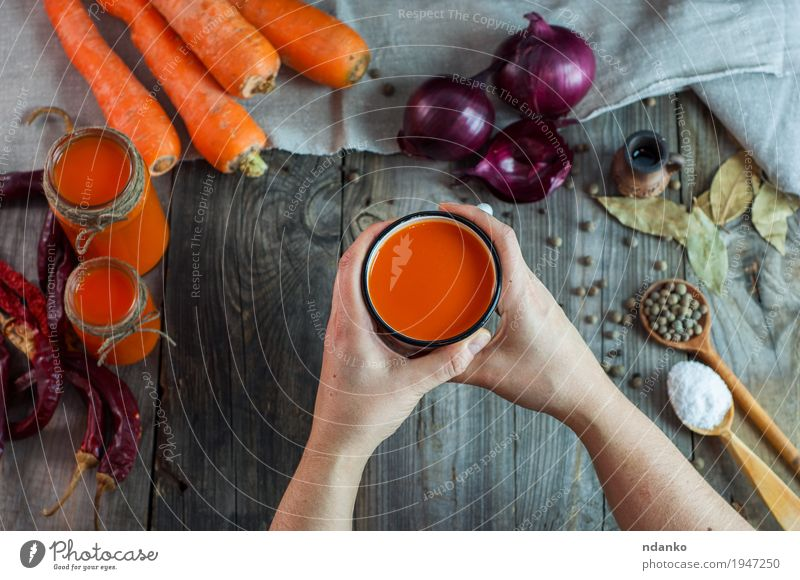 weibliche Hände, die einen Eisenbecher mit Karottensaft halten Mensch Jugendliche Junge Frau Hand Blatt 18-30 Jahre Erwachsene Holz Lebensmittel