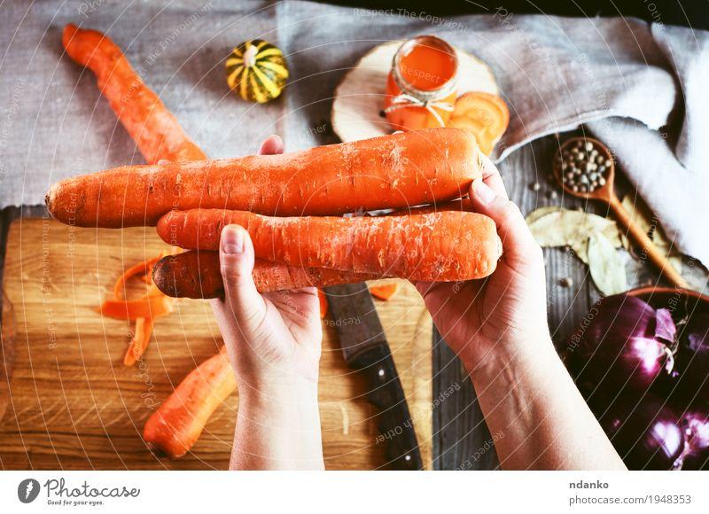 weibliche menschliche Hand, die drei große orange Karotte hält Lebensmittel Gemüse Kräuter & Gewürze Ernährung Vegetarische Ernährung Diät Getränk Saft Tisch