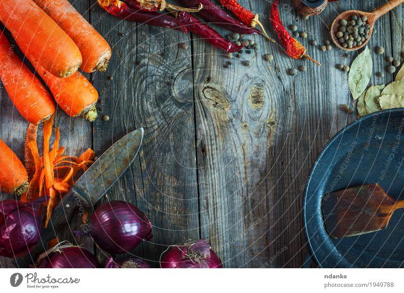 Frische Karotten und rote Zwiebel mit einer Bratpfanne Gemüse Frucht Kräuter & Gewürze Vegetarische Ernährung Pfanne Löffel Tisch Küche Holz Metall alt Essen