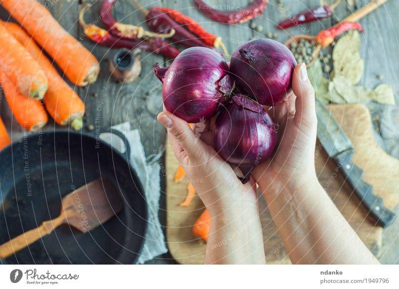 emale Hände halten drei rote Zwiebeln Lebensmittel Gemüse Kräuter & Gewürze Ernährung Vegetarische Ernährung Pfanne Messer Löffel Tisch Küche Junge Frau