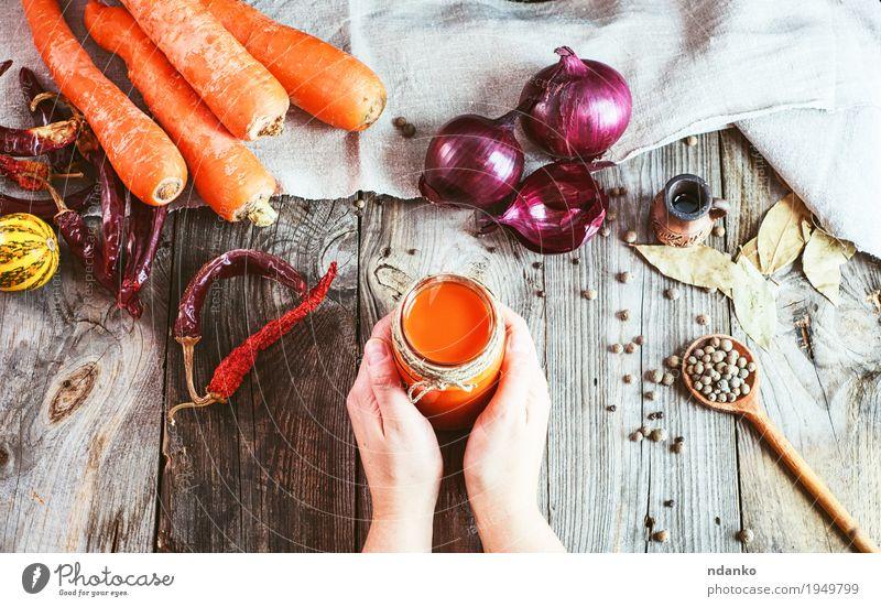 Weibliche Hände, die ein Glas mit einem Glas frischem Karottensaft halten Mensch Frau Jugendliche Hand Blatt 18-30 Jahre Erwachsene Essen natürlich Holz