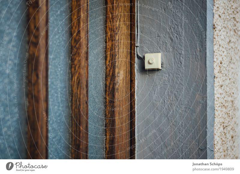 Klingel Kleinstadt Haus Einfamilienhaus Mauer Wand Tür braun grau Glastür Eingangstür Häusliches Leben Heimat wiederkommen alt Putz Fassade Holztür anonym