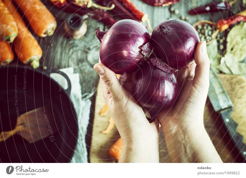 weibliche Hände halten drei rote Zwiebeln Gemüse Kräuter & Gewürze Ernährung Vegetarische Ernährung Pfanne Messer Löffel Tisch feminin Hand Finger 1 Mensch