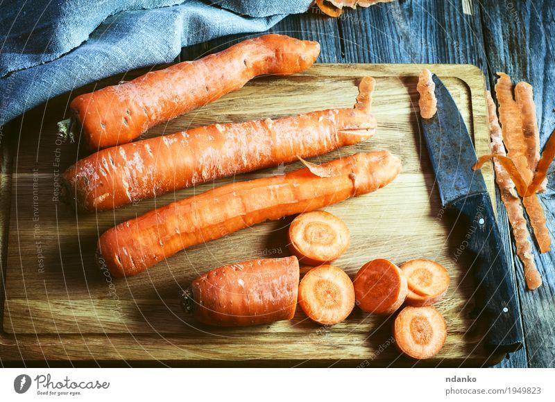 frische lange Karotte auf einem Schneidebrett Gemüse Ernährung Essen Vegetarische Ernährung Diät Tisch Natur Holz natürlich oben retro orange Tischwäsche