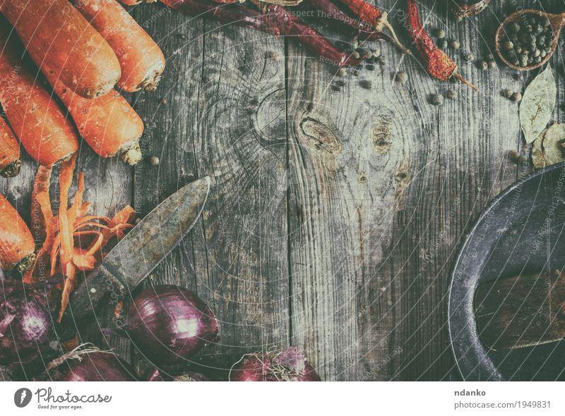 Frische Karotten und rote Zwiebel mit einer Bratpfanne Lebensmittel Gemüse Kräuter & Gewürze Vegetarische Ernährung Pfanne Löffel Tisch Küche Holz alt frisch