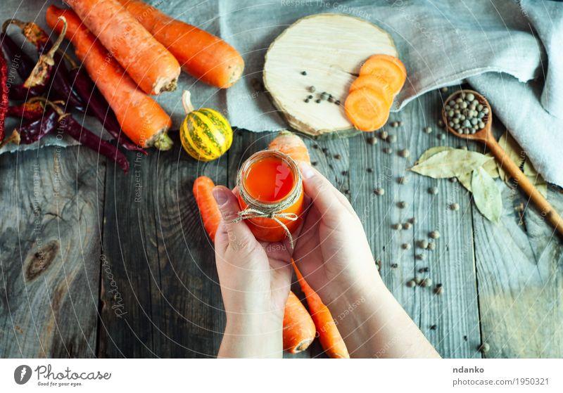 Glas frischer Karottensaft in der weiblichen Hand Mensch Frau Jugendliche alt Blatt Freude 18-30 Jahre Erwachsene Essen natürlich Holz Gesundheitswesen grau