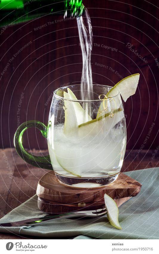 frisches Birnenwasser - Mineralwasser ergießt sich in ein Glas mit Birnenspalten vor dunklem Hintergrund Trinkwasser Frucht Getränk Erfrischungsgetränk Flasche