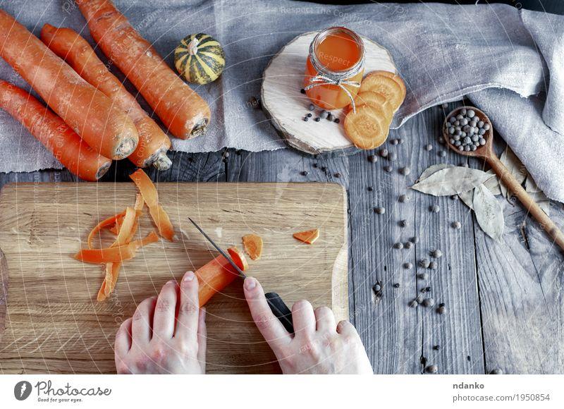 Prozess des Schneidens frischer Karotten auf einem Schneidebrett Mensch Frau Jugendliche alt Hand 18-30 Jahre Erwachsene Essen Holz Gesundheitswesen grau orange