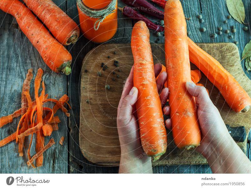 Zwei große reife Karotten liegen in den weiblichen Händen Gemüse Ernährung Vegetarische Ernährung Diät Getränk Saft Flasche Körper Gesunde Ernährung Tisch Frau