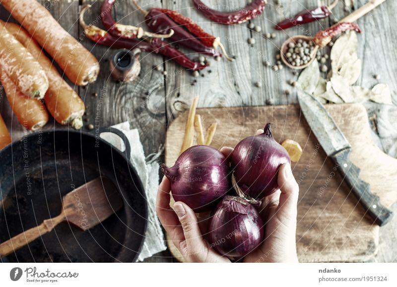 drei große rote Zwiebeln in weiblichen Händen Frau Jugendliche Hand 18-30 Jahre Erwachsene Essen Holz Lebensmittel grau braun orange frisch Tisch Finger