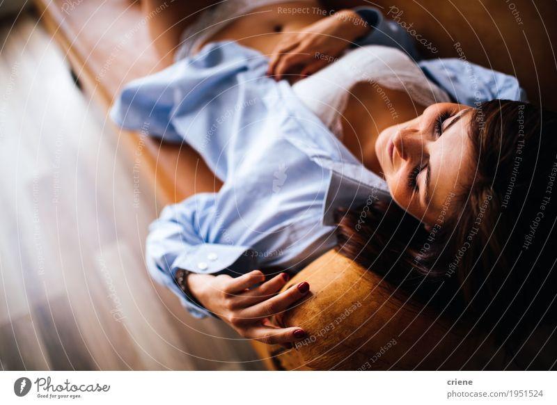 Junge kaukasische Frauen, die auf Couch legen. Lifestyle Erholung Freizeit & Hobby Häusliches Leben Wohnung Möbel Sofa Wohnzimmer Mensch feminin Junge Frau
