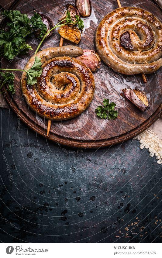 Gegrillte Bratwürste mit Knoblauch und Gewürze Lebensmittel Wurstwaren Ernährung Design Tisch Grill Stil Bratwurst Feinschmecker Snack Foodfotografie rustikal