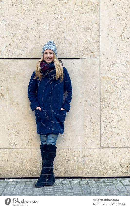 Lächelnde modische junge Frau, die gegen Wand steht Glück schön Erholung Winter Erwachsene Herbst Mode Mantel Schal Stiefel Hut blond stehen dünn trendy lang