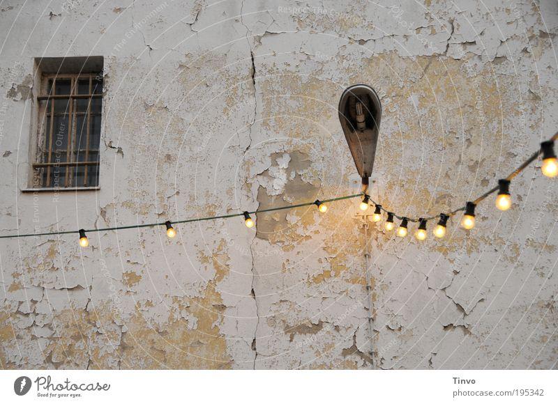 Illuminierte Lampe Mauer Wand Fassade Fenster alt dreckig Lichterkette Elektrizität Glühbirne Laterne Außenbeleuchtung vergittert Putzfassade abblättern