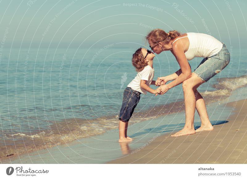 Mutter und Sohn, die auf dem Strand zur Tageszeit spielen. Kind Frau Natur Ferien & Urlaub & Reisen Sommer Sonne Hand Meer Erholung Freude Erwachsene Leben