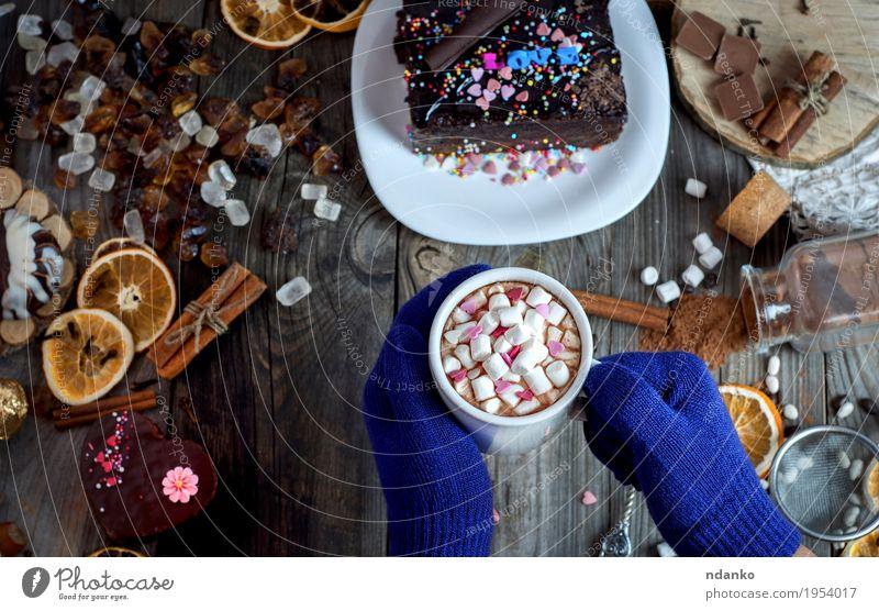 Paar weibliche Hände mit den blauen Handschuhen, die einen Becher halten Frucht Orange Dessert Kräuter & Gewürze Frühstück Getränk Heißgetränk Kakao Kaffee