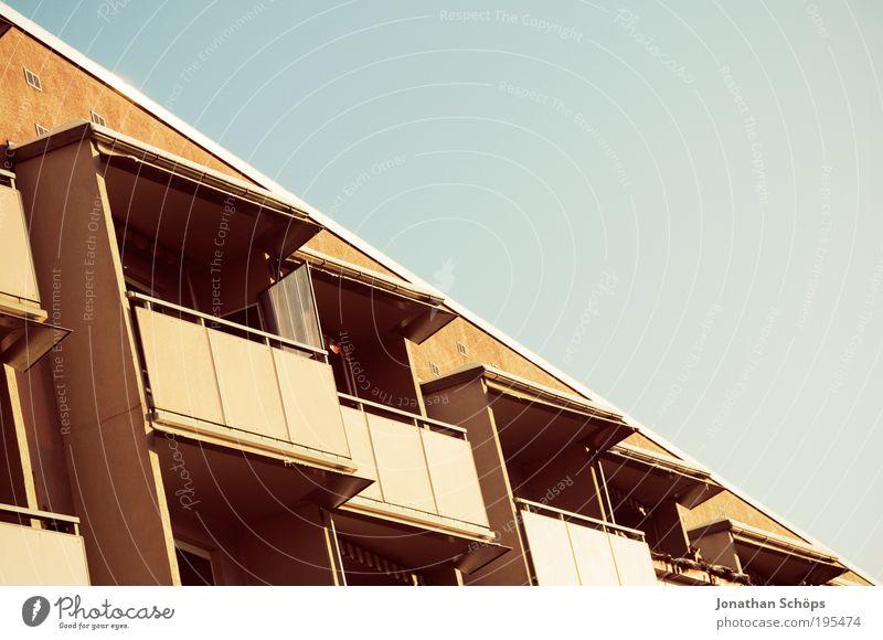 Haus \ Himmel Stadt Stadtrand Balkon blau braun gold sparsam stagnierend Symmetrie Plattenbau 50% Teilung Ghetto DDR Wohnsiedlung gleich trist Farbe