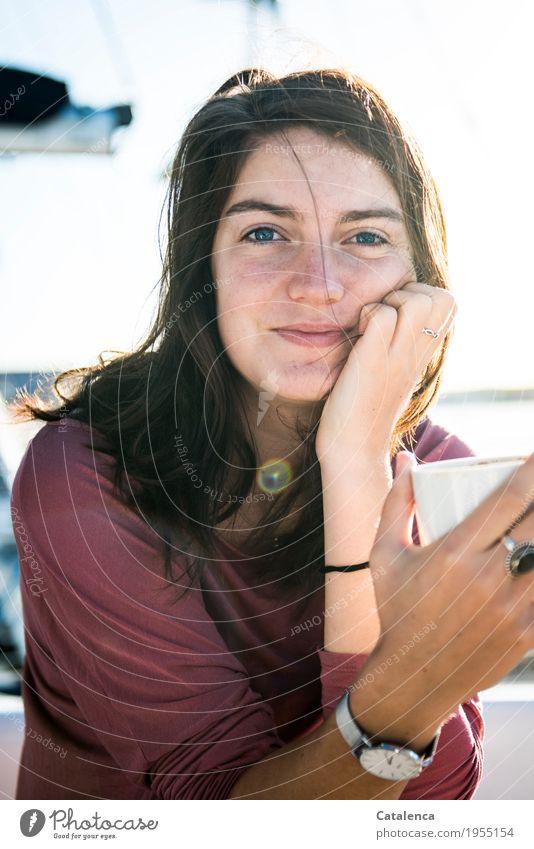 Eine junge Frau schaut lächelnd in die Kamera trinken Kaffee Segeln Sommer Meer Jachthafen Kaffeetasse beobachten genießen Duft schön blau braun rosa Stimmung