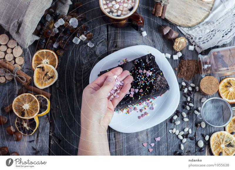 Weibliche Hand besprüht Zuckerherzenstück von Sachertorte Frucht Kuchen Dessert Süßwaren Essen Frühstück Getränk Kakao Kaffee Teller Besteck