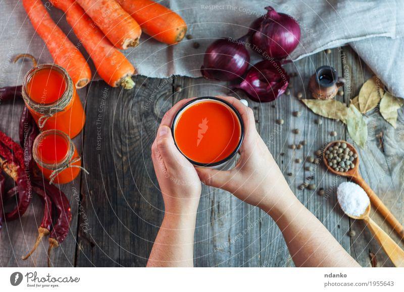 Eisen-Becher mit Karottensaft in weiblichen Händen Lebensmittel Gemüse Kräuter & Gewürze Ernährung Getränk Erfrischungsgetränk Saft Tasse Löffel Tisch Frau