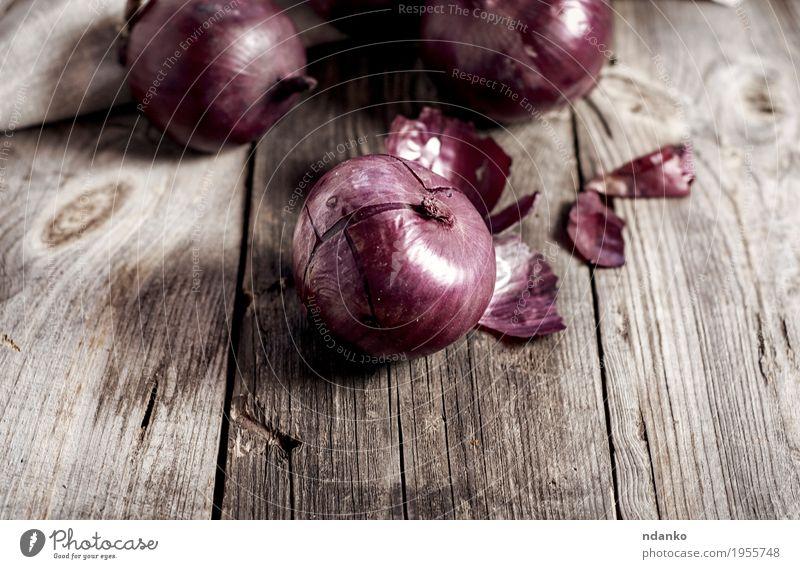 Rote Zwiebeln in der Hülse auf der grauen Holzoberfläche Gemüse Vegetarische Ernährung Pflanze alt dunkel frisch braun rot reif Knolle organisch Salatbeilage
