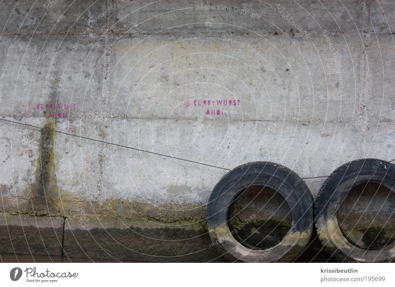 Currywurst I Ferien & Urlaub & Reisen Wand Graffiti grau Stein Mauer lustig rosa dreckig Beton trist entdecken skurril Reifen Rätsel Autoreifen