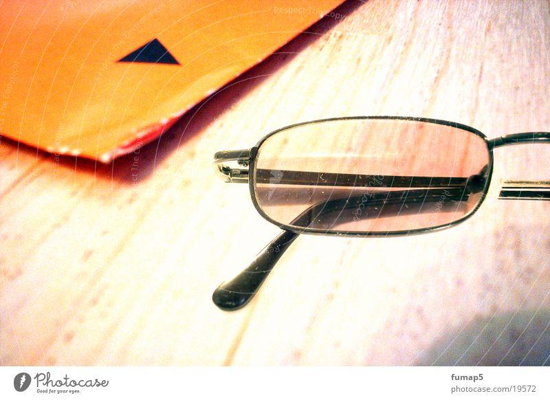 die brille Brille schwarz Briefumschlag Holz Tisch Makroaufnahme Nahaufnahme