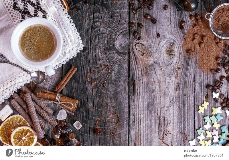 Grauer hölzerner Hintergrund mit schwarzem Kaffee Lebensmittel Frucht Dessert Süßwaren Frühstück Kaffeetrinken Getränk Heißgetränk Kakao Espresso Becher Löffel