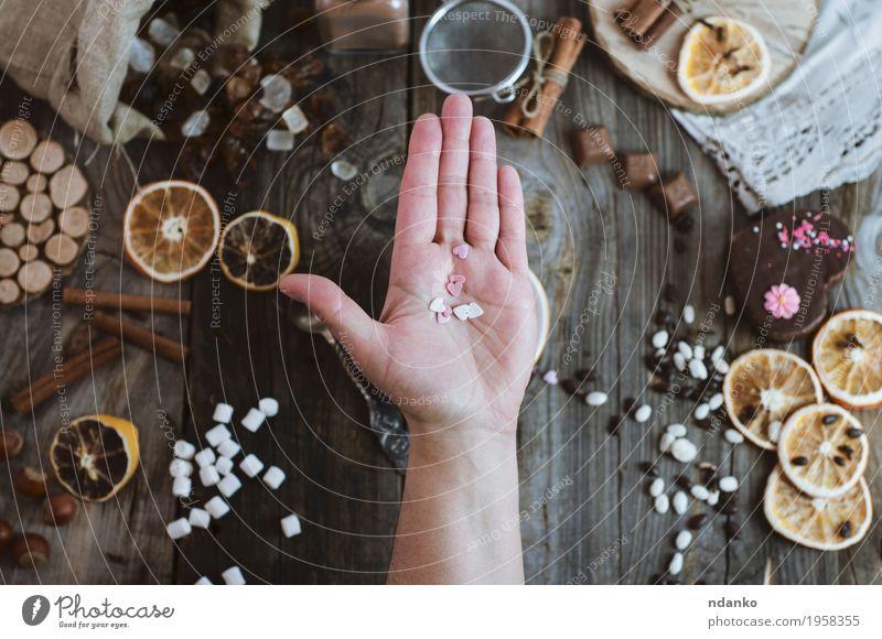Öffnen Sie menschliche Palme auf dem Hintergrund der Tabelle mit Bonbons Mensch Frau Jugendliche weiß Hand 18-30 Jahre Erwachsene Essen Holz grau braun oben
