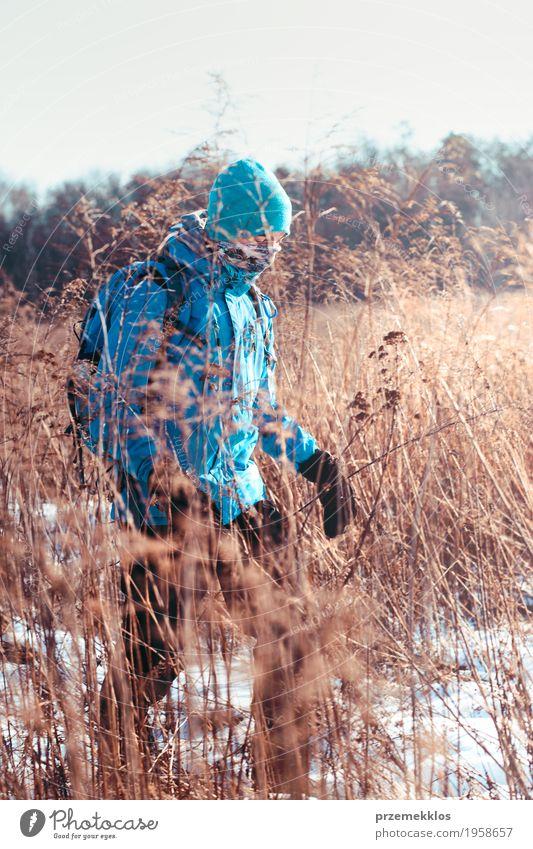 Junge, der durch Wiesen in der Winterzeit wandert Mensch Natur Ferien & Urlaub & Reisen Jugendliche Landschaft Einsamkeit Freude Lifestyle Schnee Sport Gras