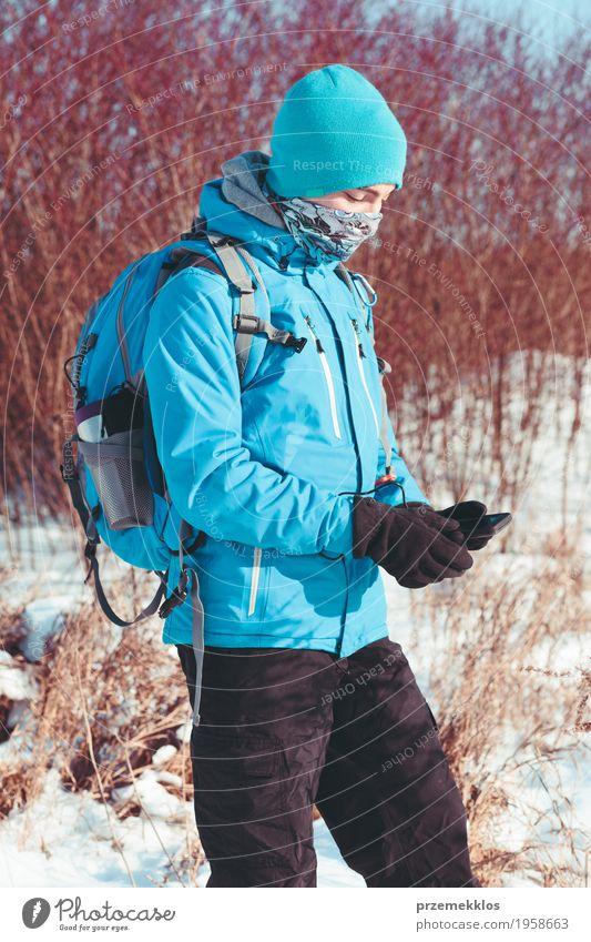 Junge, der den Handy während der Winterreise verwendet Lifestyle Freude Ferien & Urlaub & Reisen Ausflug Abenteuer Freiheit Expedition Schnee Winterurlaub