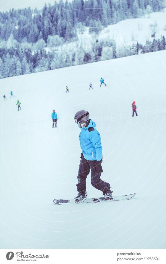 Junge, der einen Snowboard den Abhang hinunter reitet Freude Ferien & Urlaub & Reisen Winter Schnee Winterurlaub Berge u. Gebirge Sport Natur Landschaft Hügel