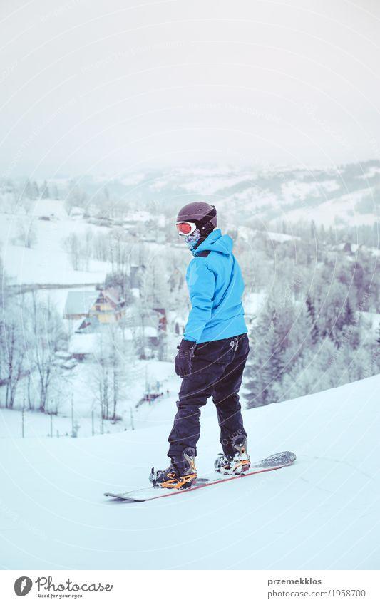 Junge, der einen Snowboard den Abhang hinunter reitet Lifestyle Freude Ferien & Urlaub & Reisen Winter Schnee Winterurlaub Berge u. Gebirge Sport Natur
