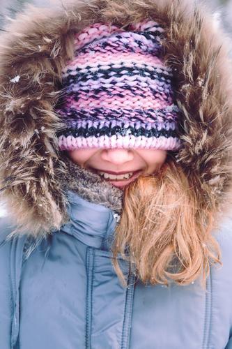Portrait des Mädchens mit abgedecktem Gesicht mit ihrem Hut draußen Mensch Kind Frau Freude Winter Erwachsene Lifestyle Schnee Glück Kindheit Fröhlichkeit