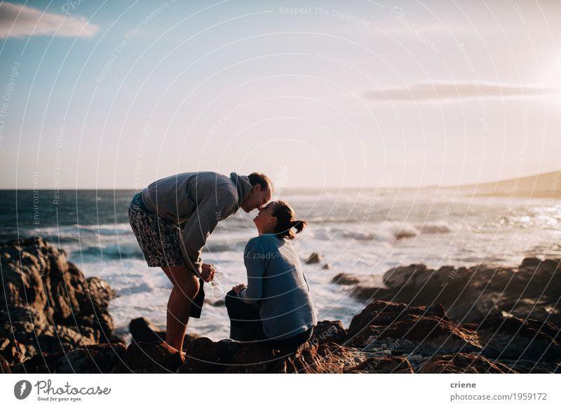 Kaukasische Paare des jungen Erwachsenen, die auf Klippe in Ozean küssen Mensch Ferien & Urlaub & Reisen Jugendliche Junge Frau Junger Mann Meer Freude Strand