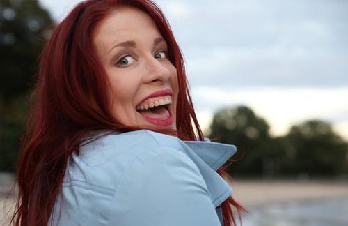 . feminin Frau Erwachsene 1 Mensch Schönes Wetter Wald Küste Flussufer Strand Mantel rothaarig langhaarig entdecken lachen Blick schön Freude Fröhlichkeit