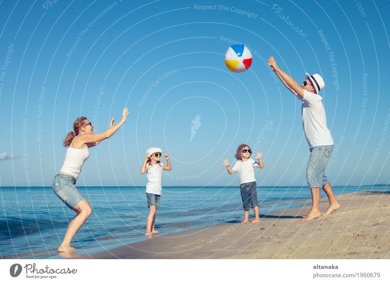 Glückliche Familie, die auf dem Strand zur Tageszeit spielt. Kind Frau Natur Ferien & Urlaub & Reisen Sommer Sonne Meer Erholung Freude Mädchen Erwachsene Leben