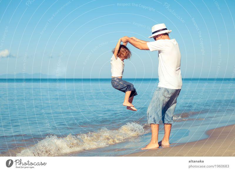 Vater und Sohn, die auf dem Strand zur Tageszeit spielen. Kind Natur Ferien & Urlaub & Reisen Mann Sommer Sonne Hand Meer Erholung Freude Erwachsene Leben Liebe